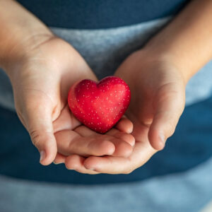 Close up of boy hands holding a red heart shape. Top view of child hands showing small red heart. High angle view of kid hands holding a heart-shaped stone at home, symbol of love and care.